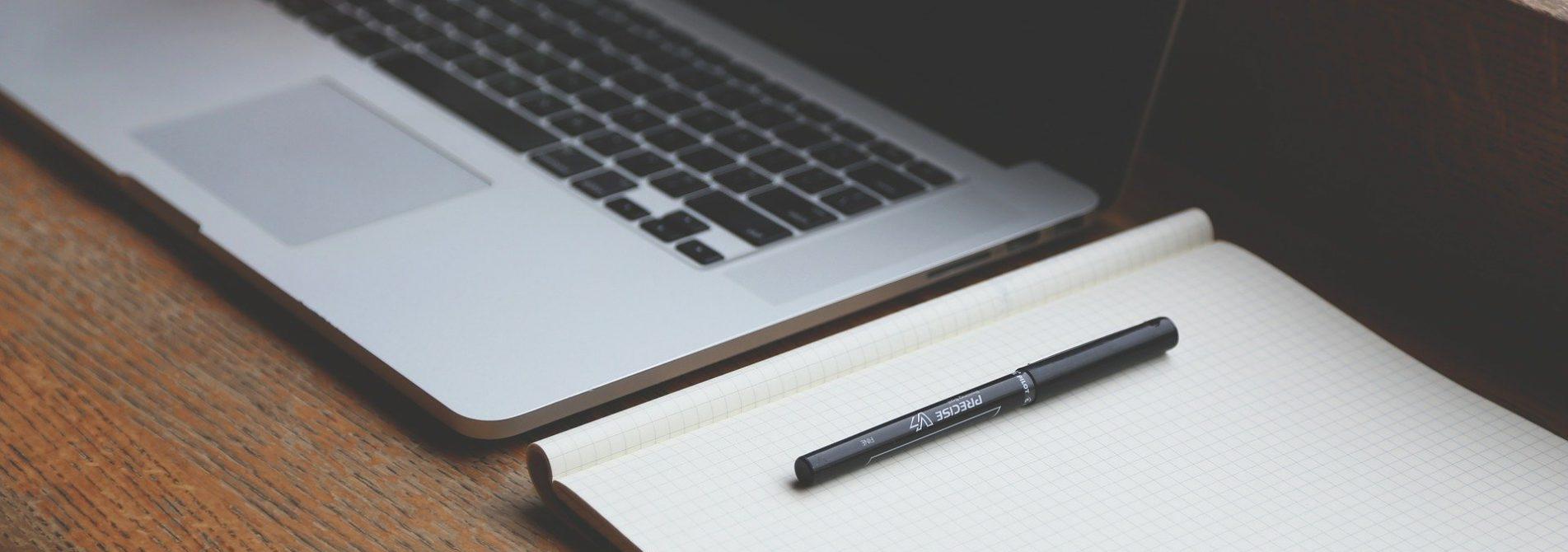 Computador e caderno de trabalho